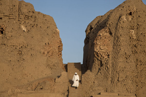 Sudanese in white robe descending from the western deffufa | Deffufas van Kerma | Soedan