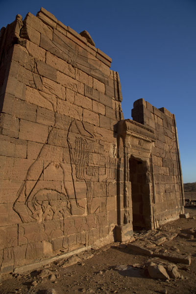 The entrance of the Lion Temple with larger than life carved figures in the wall | Naqa | Sudan