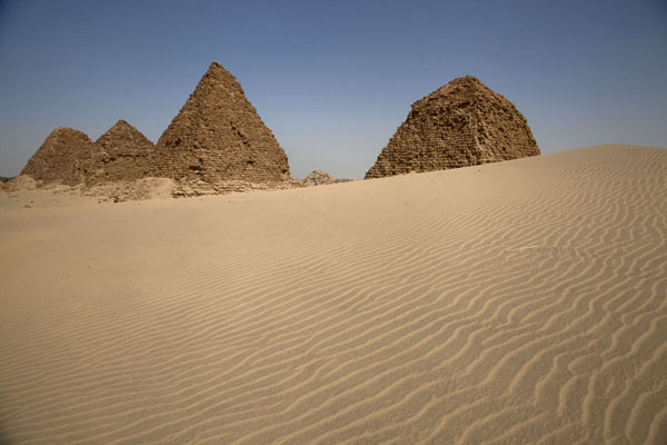Sand dune with pyramids behind it | Nuri pyramids | Sudan