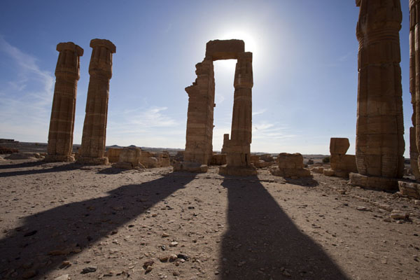 The sun sinking behind the massive columns of the temple of Soleb | Soleb | Soedan