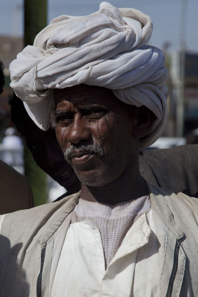 Man with typical white turban in the streets of Kassala | Sudanesi | Sudan