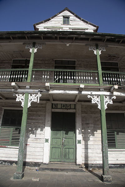 Picture of Morning sun shining on a wooden white-and-green building in Paramaribo