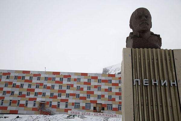 Foto de Lenin on the main square of Barentsburg with a communist slogan and the first arctic skyscraper in the background -  - Europa