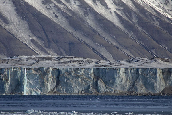 Wall of blue ice of Negribreen glacier with diagonally striped mountain behind | Negribreen glacier | Svalbard and Jan Mayen