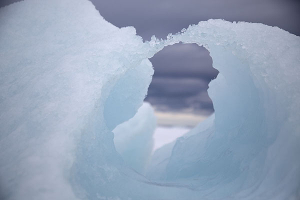 Looking through a hole in an iceberg in Storfjorden | Motoneige à la côte de l'est de Spitsbergen |