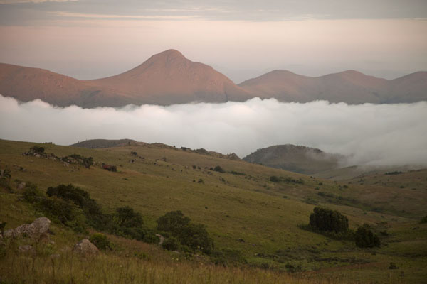 Picture of Sun rising over the mountains of Malolotja with clouds hanging in the valley below - Swaziland - Africa