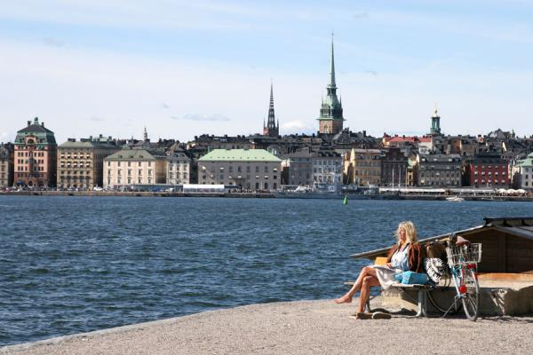 Picture of Stockholm waterfront (Sweden): Swedish woman enjoying the sun; Gamla Stan in the background