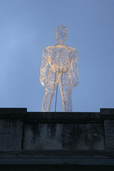 Iron sculpture or traveller standing on the roof of a building | Yalil Sculptures | Switzerland