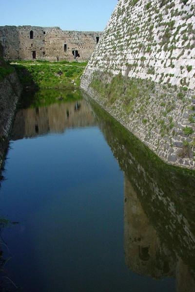 Part of the wall and towers reflected in the moat | Krak des Chevaliers | Syria