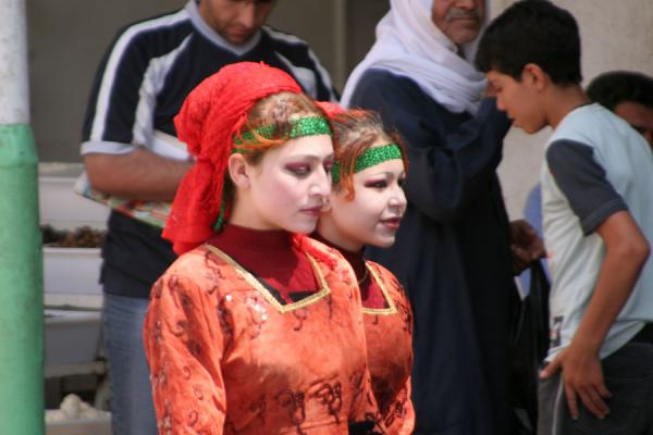 Photo de Syrie (Syrian women in bright red dresses in the streets of Deir es Zor)