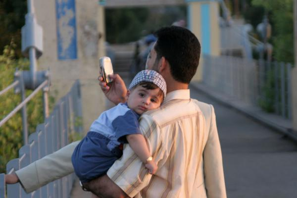 Picture of Syrian people (Syria): Mobile communication with child on shoulder on bridge over Euphrates River