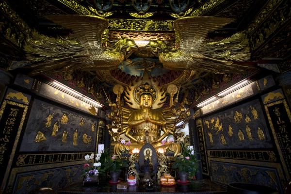Picture of Guandu temple (Taiwan): Statue of Guanyin, goddess of mercy with lavishly decorated ceiling near the balcony of Guandu temple