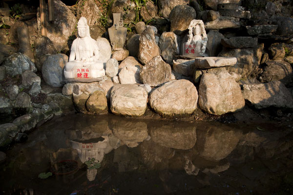 Foto de Buddha statues reflected in a pond at the Shifen waterfallSandiaoling - Taiwán