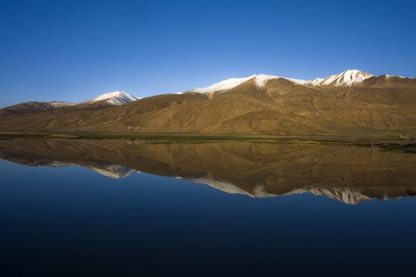 Foto di Tagikistan (Early morning light on a mirrored mountain near Bulunkul)