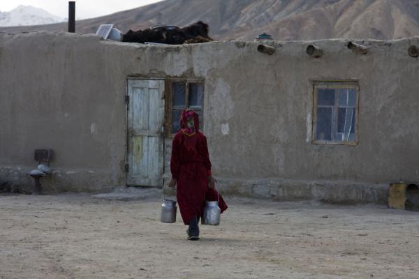 Picture of Bulunkul (Tajikistan): Woman with buckets walking towards her house in Bulunkul