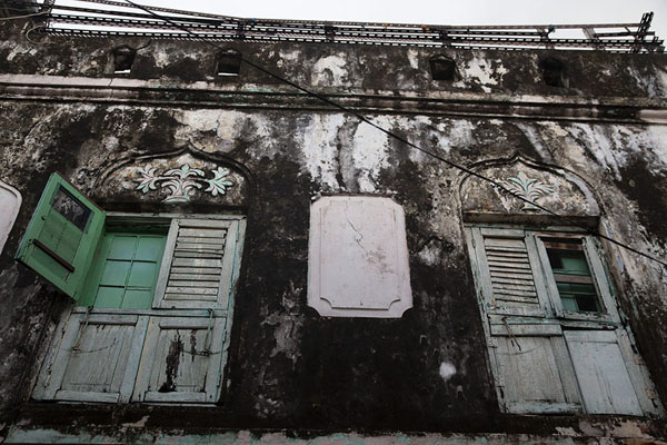 Picture of Looking up a house in Stone Town with two windows with shutters