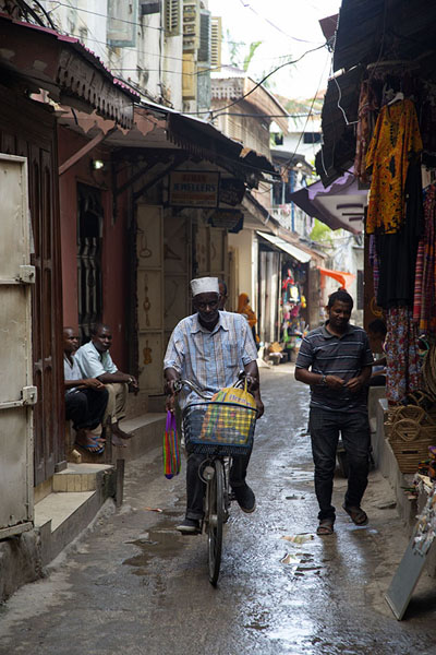 Picture of Alley in Stone Town with cyclist, pedestrians, and shops - Tanzania - Africa