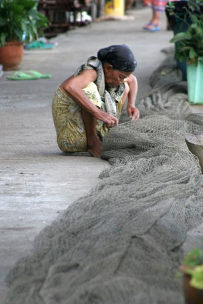 Picture of Ko Panyi (Thailand): Ko Panyi: woman adjusting the nets in one of the streets