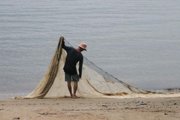 Picture of Thai Fishermen (Thailand): Fishermann arranging his nets on the beach near Ban Phe