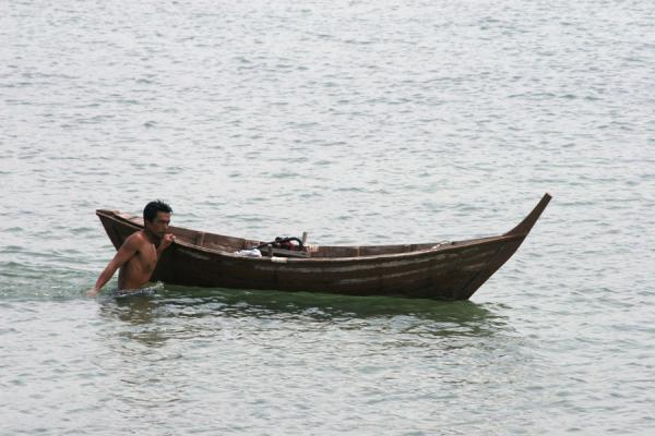 Picture of Thai Fishermen (Thailand): Lone fisherman dragging his boat in the sea at Ko Mook