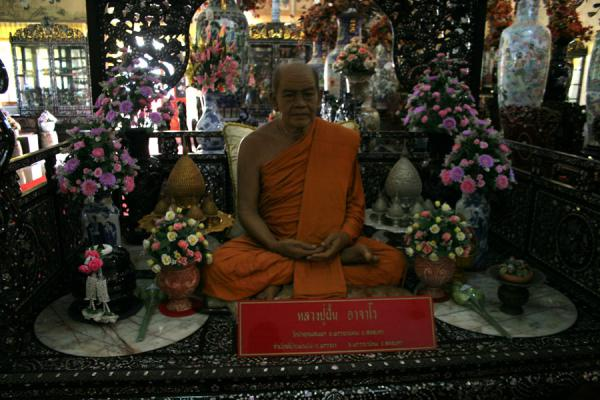 Picture of Wat Khao Sukim (Thailand): Wax monk surrounded by presents in Wat Khao Sukim