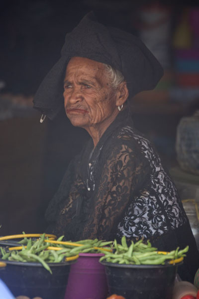 Older woman waiting for customers at a stall of the market of Maubisse | Maubisse market | 帝汶勒斯特