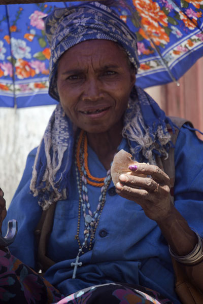 Woman offering bread from under an umbrella | Marché de Maubisse | Timor Oriental