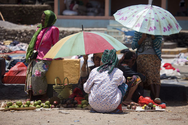 Women hiding under umbrellas to protect against the rays of sun | Maubisse market | 帝汶勒斯特