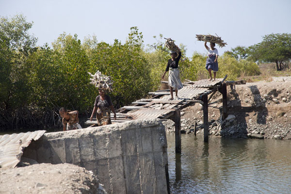Foto van Women crossing a bridge over a lagoon with crocodilesSuai Loro - Oost Timor