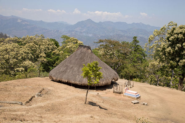 的照片 帝汶勒斯特 (Traditional thatched hut with grave and mountains in the background, typical scenery in western East Timor)