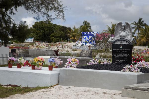 Picture of Tongan cemeteries (Tonga): Tombstone with angel and more traditional graves with banners and sand in Nuku'alofa
