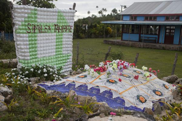 Picture of Banner over a grave covered in a blanket with flowers on Vava'u islandTonga - Tonga