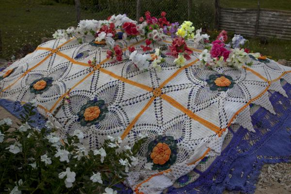 Picture of Tongan cemeteries (Tonga): Fake flowers on blanket covering a grave on Vava'u island
