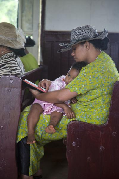 Picture of Tongan church services (Tonga): Dressed in green with hat and child on her lap, reading the bible during service