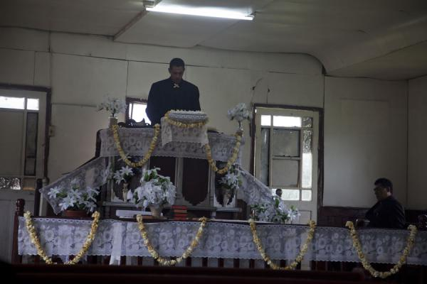 Picture of Tongan church services (Tonga): Priest surrounded by white flower decorations during service on 'Eua island