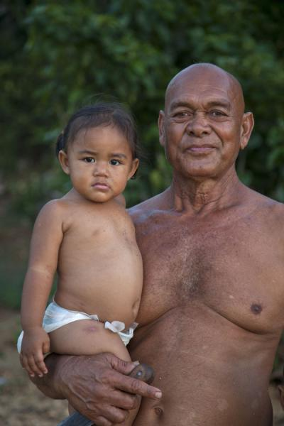 Grandfather showing his granddaughter in 'Utulei on Vava'u | Les Tonganais | Tonga