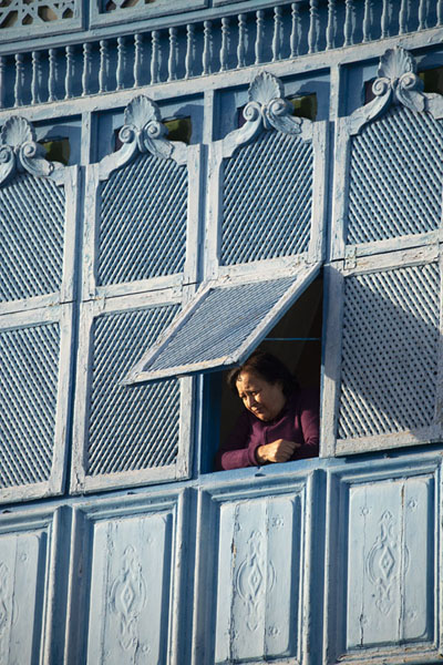 Foto van Woman peeking through a window of a blue wooden balcony in Sidi Bou SaidSidi Bou Said - Tunesië