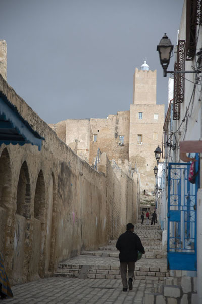 Man walking a street in Sousse with a tower of the castle in the background | Sousse medina | Túnez