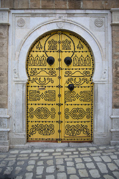 Intricate patterns with nails on a yellow door in Tunis | Tunesische deuren | Tunesië