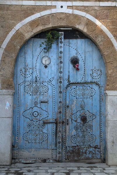 Picture of Tunisian doors (Tunisia): Blue arched door with smaller door, embellished with nail patterns