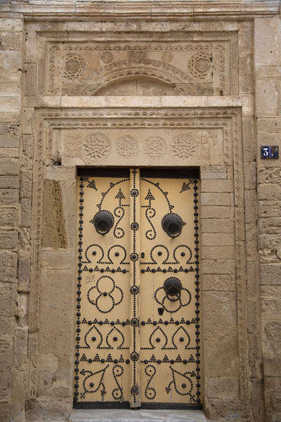 Yellow door with elaborately decorated frame in a house in Sousse | Porte tunisine | Tunisia