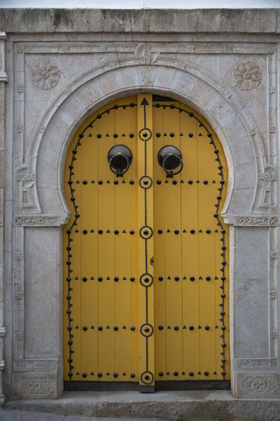 Foto de Yellow door embellished with black nails in TunisPortas tunecinas - Túnez