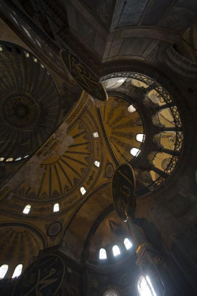 Foto de Looking up the domes and semi-domes, with decorations and columns, of the Aya SofiaAya Sofia - Turquía