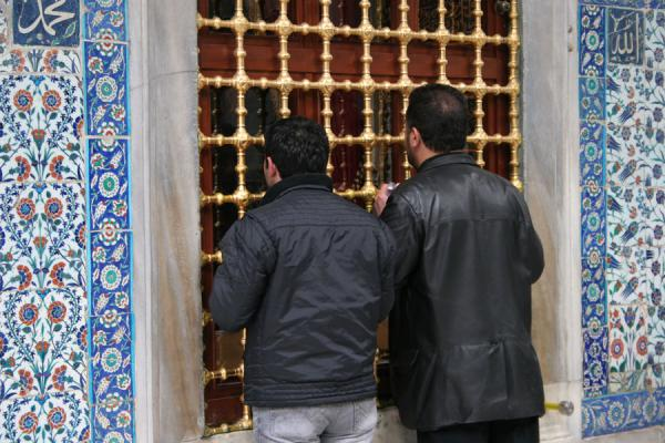 Foto van Praying through the grille in the building containing the tomb of Ayyub al-AnsariMoskee Sultan Eyüp - Turkije