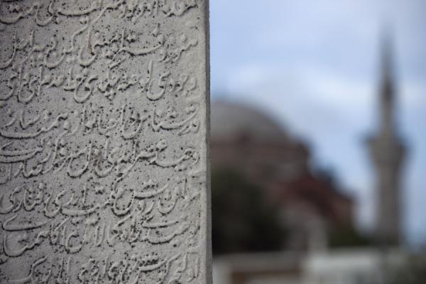 Foto van Arabic calligraphy on a tombstone at Şemsi Paşa Camii with minaret and dome of other Rumi Mehmet Paşa Camii mosque in the backgroundIstanboel - Turkije