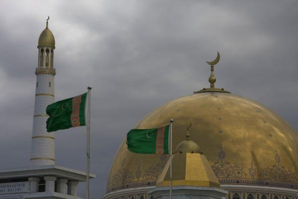 Picture of Turkmen flags, gold-and-white minaret and golden dome of Turkmenbashy Ruhy mosque