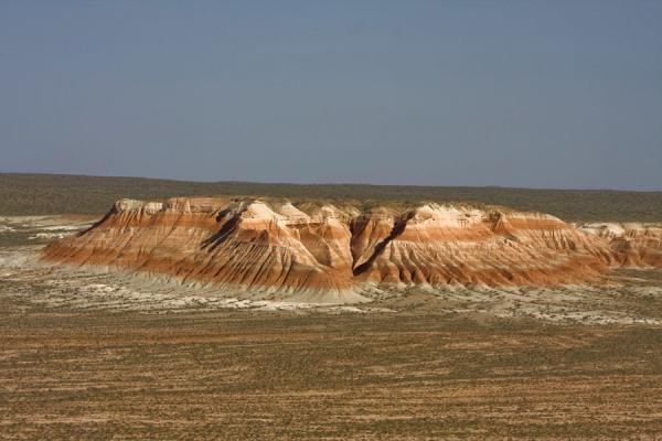Rising out of the green plains: red and white rock formations | Yangykala Canyon & Gozli Ata | Turkmenistan