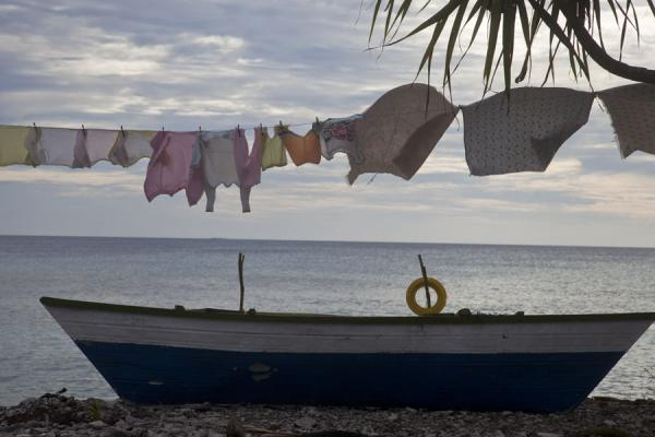 Picture of Small fishing boat with laundry drying at the coastlineFongafale - Tuvalu