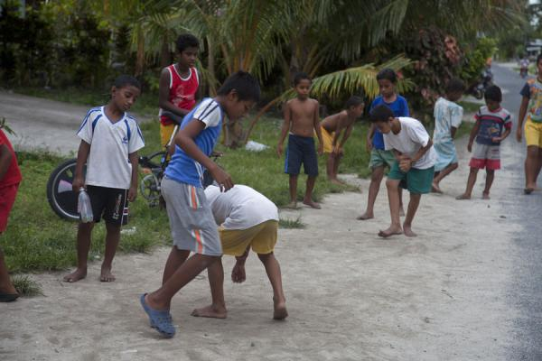 Tuvaluan boys playing marbles in the street | Tuvaluan people | Tuvalu