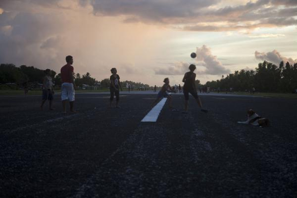 Foto di A dog watches patiently while young Tuvaluans play rugby on the runway - Tuvalu - Oceania